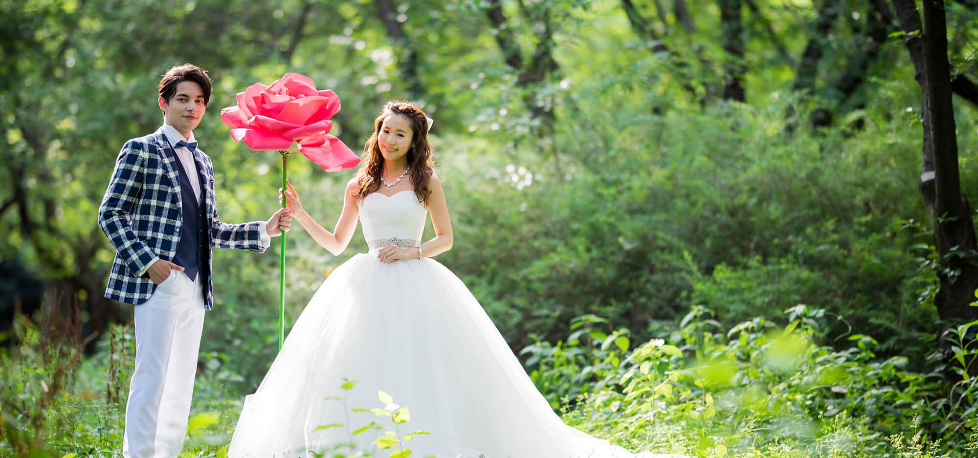 緑が鮮やかな自然の中で、白いウェディングドレス姿の花嫁と